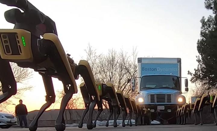 Imagem de 10 robôs SpotMini da Boston Dynamics a rebocar um camião