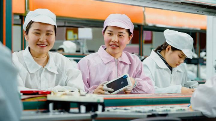 Imagem trabalhadoras a fabricar o smartphone da Apple na China