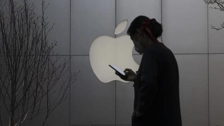 Imagem utilizadora com proteção contra o Coronavírus junto a uma loja da Apple na China