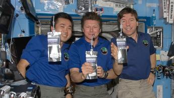 Imagem de astronautas a beber água reciclada na Estação Espacial Internacional