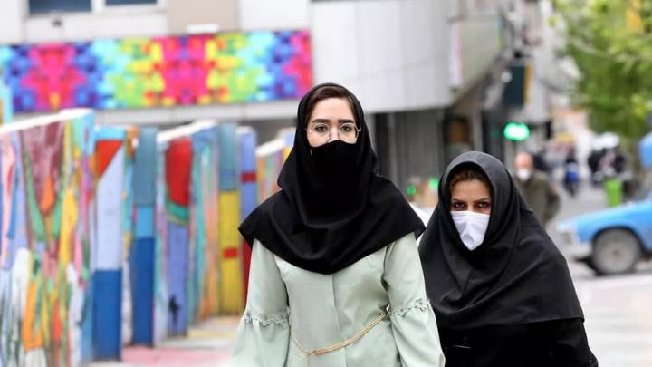 Imagem de pessoas no Irão protegidas da pandemia com máscara