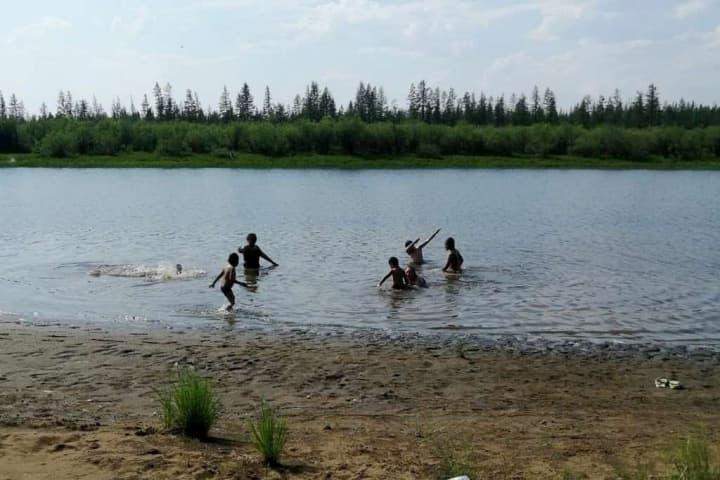 Imagem crianças a brincar num lago em Verkhoyansk, Rússia.