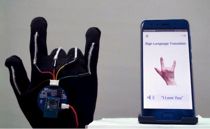 Luva com fios elétricos e sensores e smartphone com deteção dos movimentos da luva.