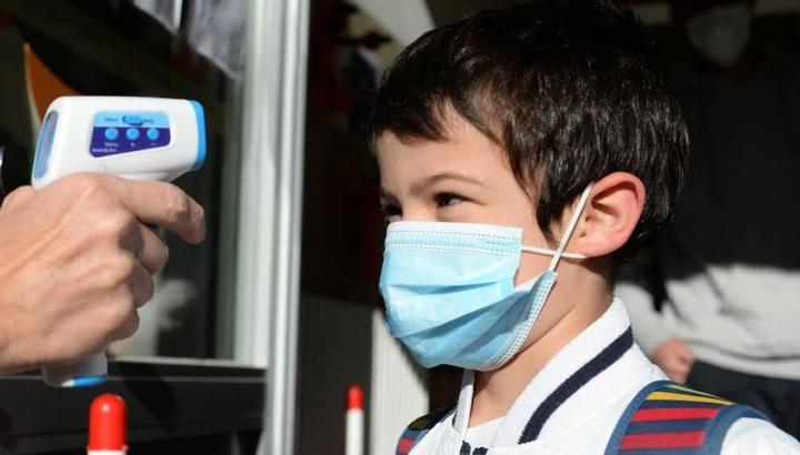 Imagem de uma criança a ser examinada à sua temperatura corporal para despiste do novo coronavírus