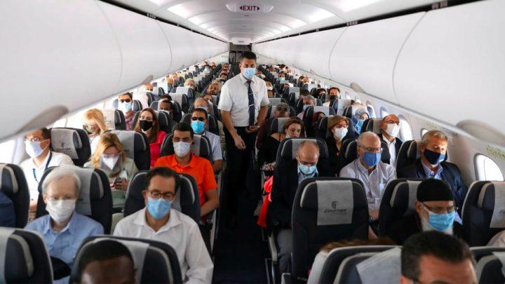 Imagem do interior de avião com pessoas a usar medidas contra a COVID-19